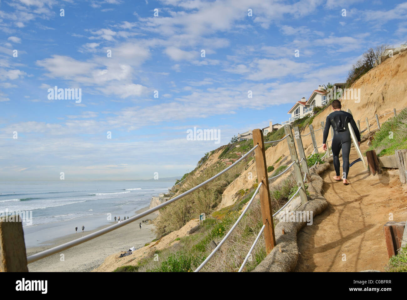 Surfers climbing a coastal bluff trail at Beacons Beach in Encinitas, California. - Stock Image