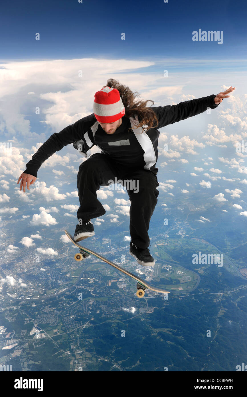 Skateboarder high above the clouds performing a trick - Stock Image