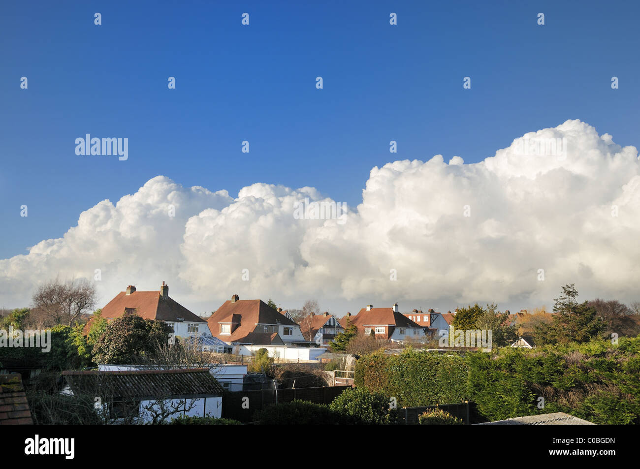 Cumulus clouds formed above English style houses - Stock Image
