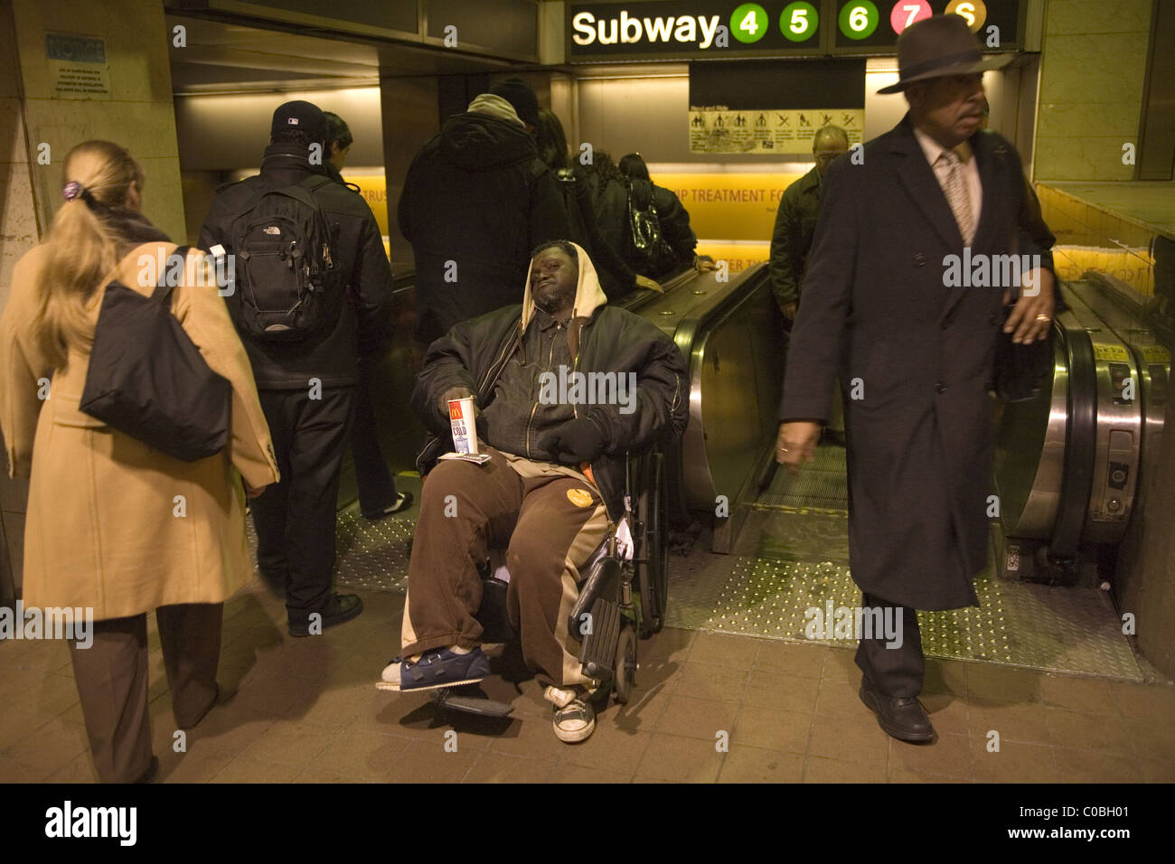 Severely disabled man in wheel chair begs for money at Grand Central Station, New York City. - Stock Image