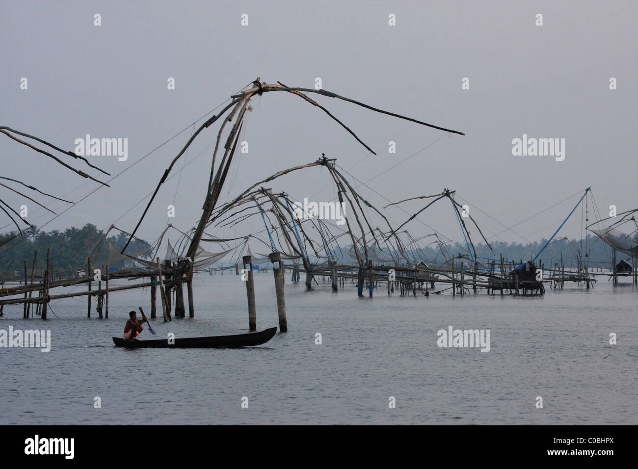 fisher man in a wooden boat from a chinese fish nets in kerala,india - Stock Image