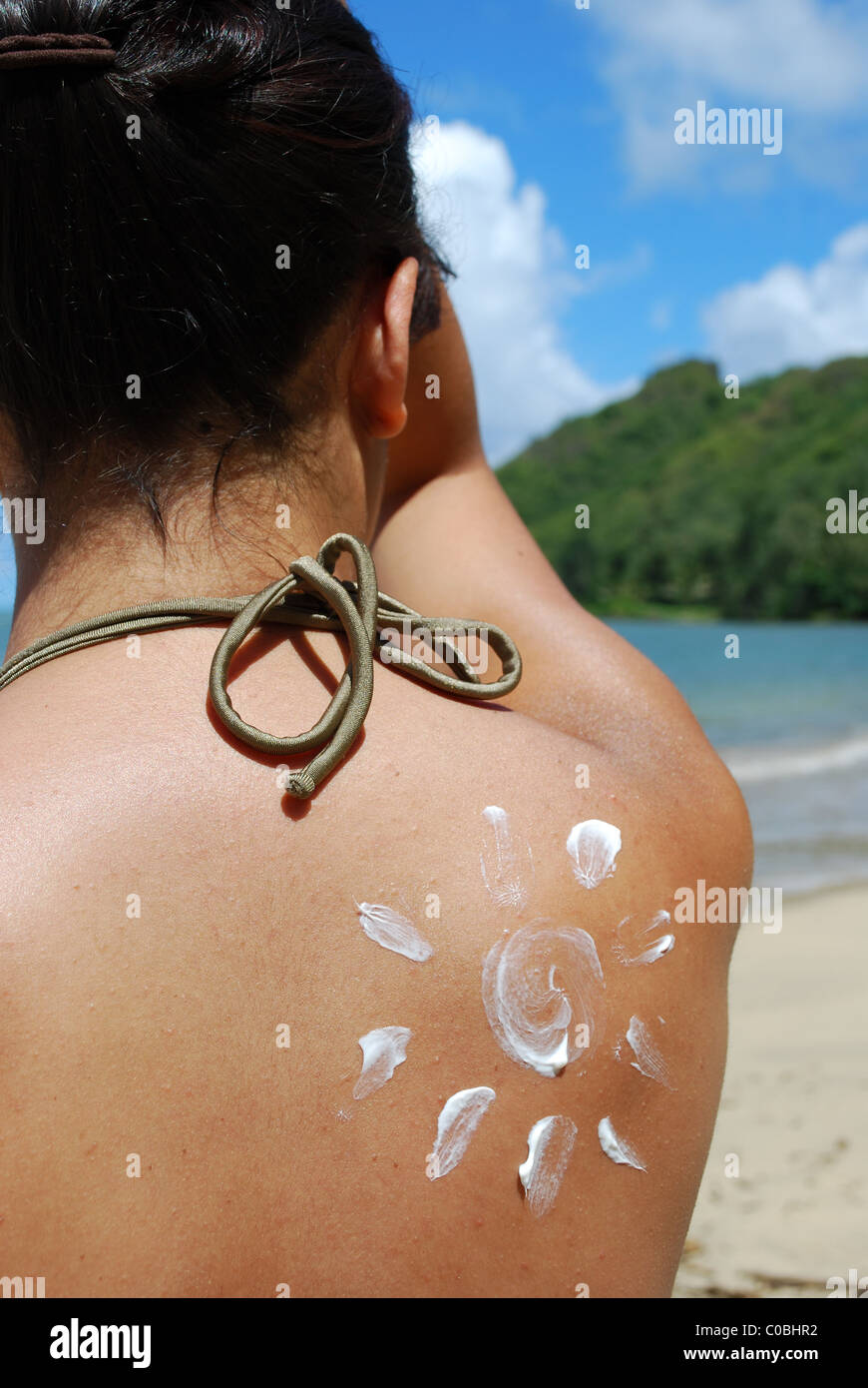 Sunscreen sun. Woman on beach in swimsuit with sun drawn in sunblock on shoulder. Oahu Hawaii. - Stock Image