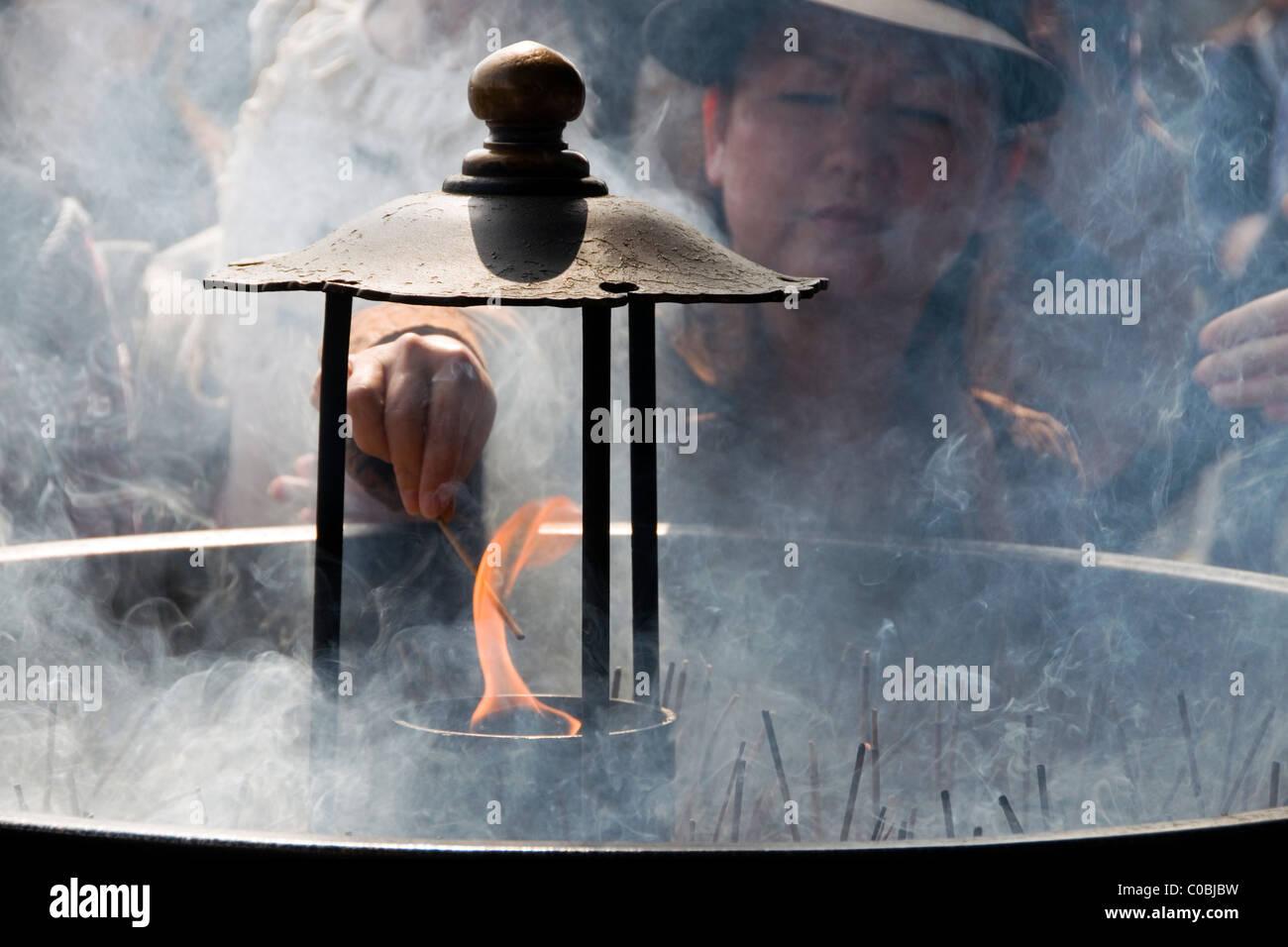 Woman burning incense for ritual purification before visiting the Great Buddha at Tōdai-ji, Nara, Japan - Stock Image