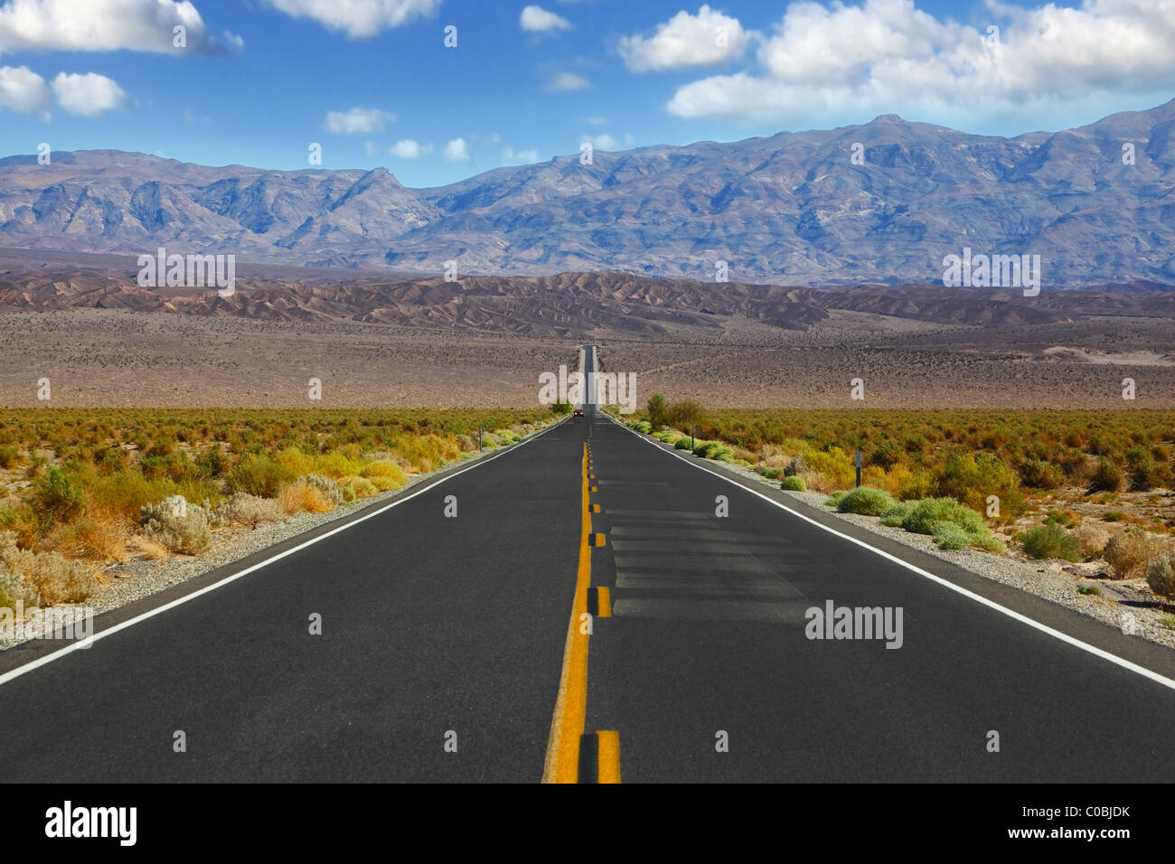 The lonely red car on the road, crossing enormous Death the Valley in California. - Stock Image