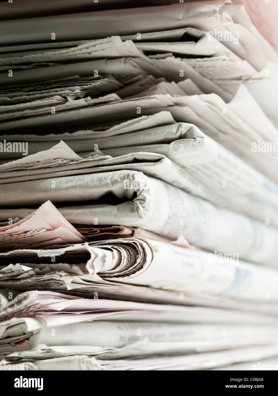 Old newspaper stacked in pile for recycling. Studio shot with selective focus and copy space - Stock Image