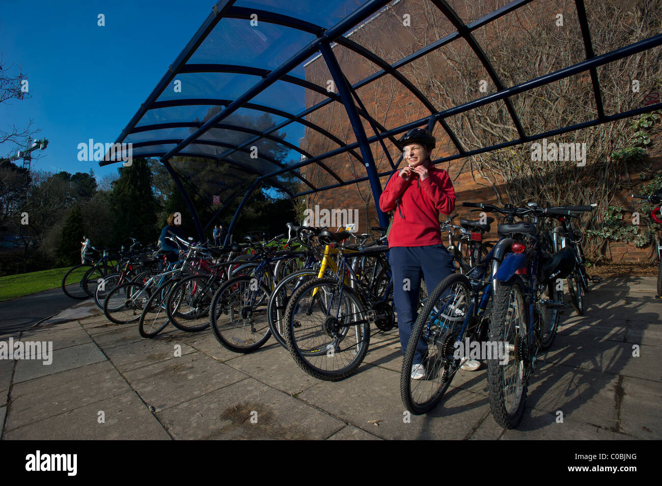 A female student standing in a bike park after riding into the campus at the University of Exeter, devon - Stock Image