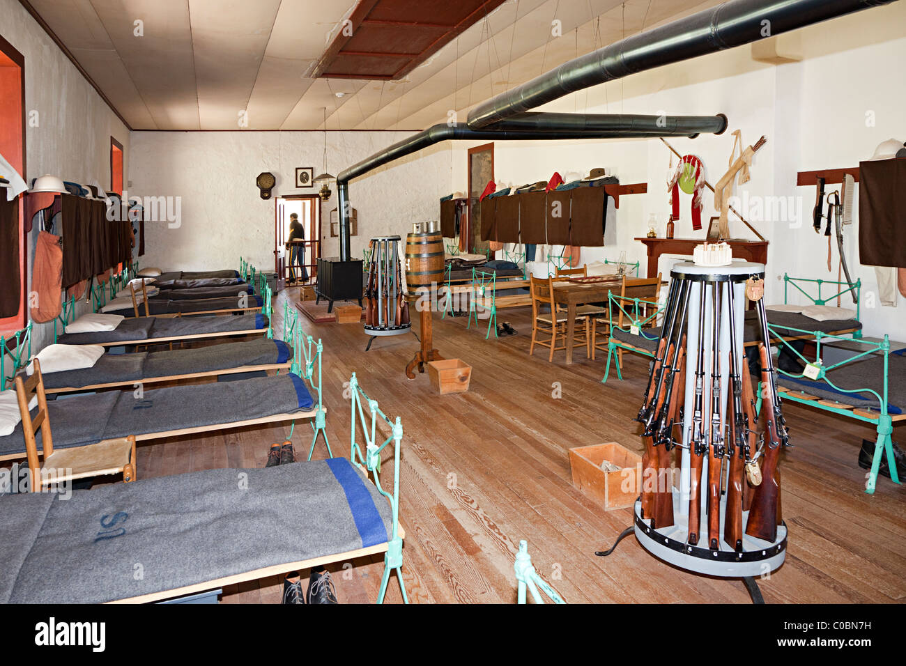 Soldiers barracks room with gun rack and beds Fort Davis National Historic Site Texas USA - Stock Image