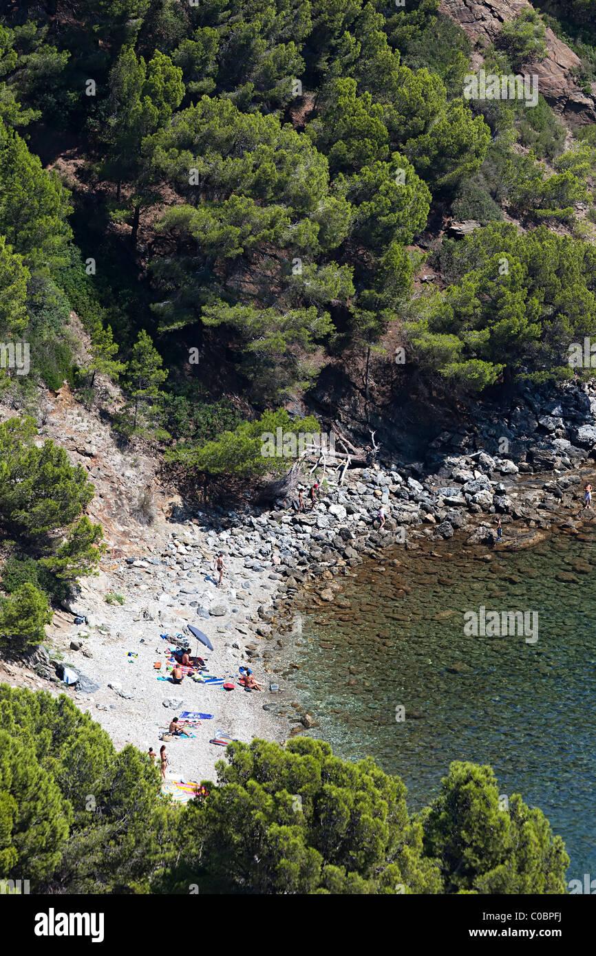 People on secluded beach on Mediterranean coast Cala Rostella Parc Natural de Cap de Creus Emporda Catalunya Spain - Stock Image