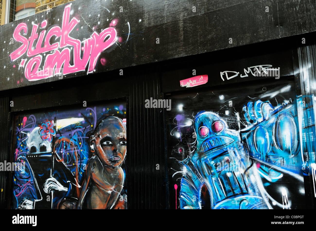 Stick 'em Up Shopfront Graffiti, off Brick Lane, London, England, Uk - Stock Image