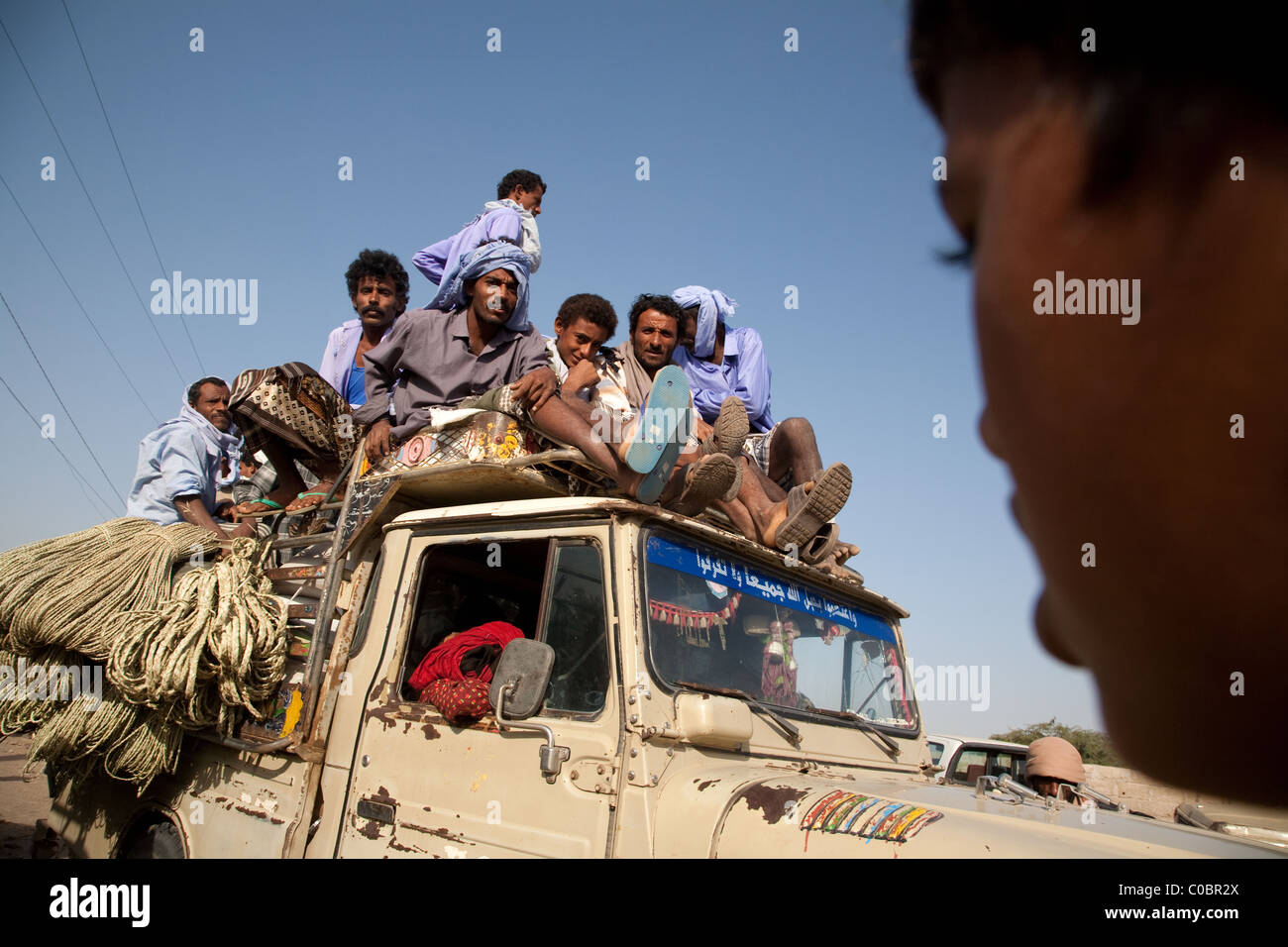 People arrive on a roof of a small truck at the Friday market in Beit al-Faqih, Yemen - Stock Image