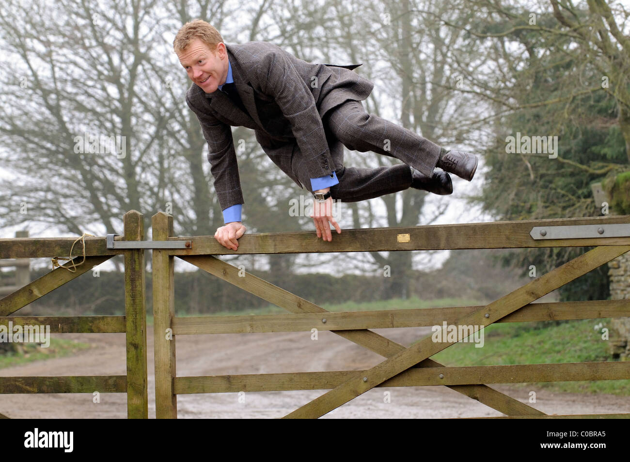 Adam Henson Cotswold farmer and tv presenter jumps his farm gate wearing a bespoke Savile Row tailored suit - Stock Image