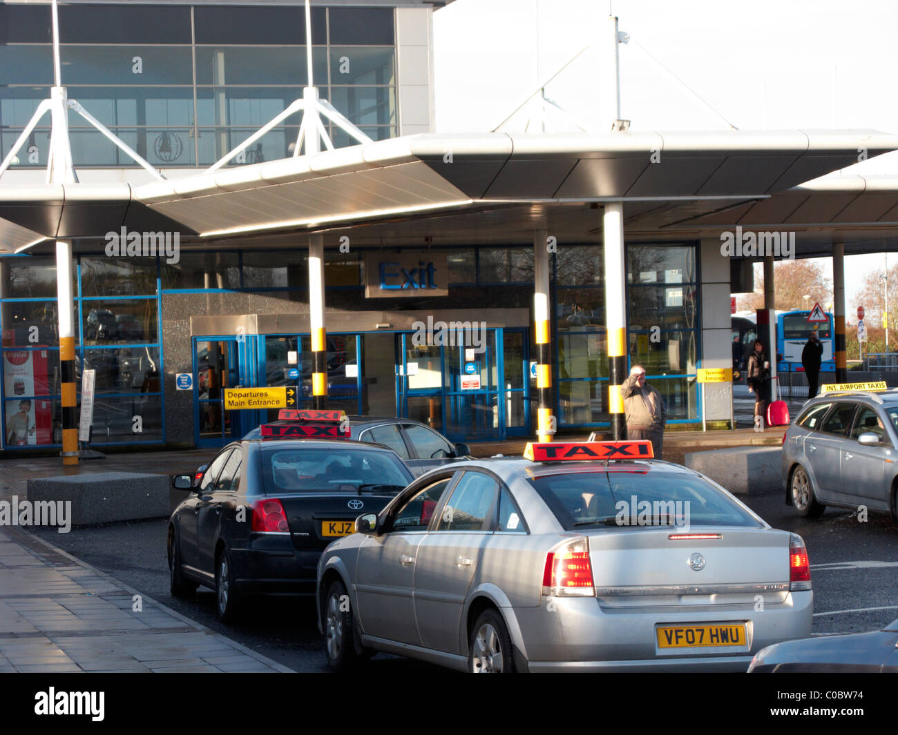 taxis queue at the exit of Belfast International Airport Northern Ireland Stock Photo