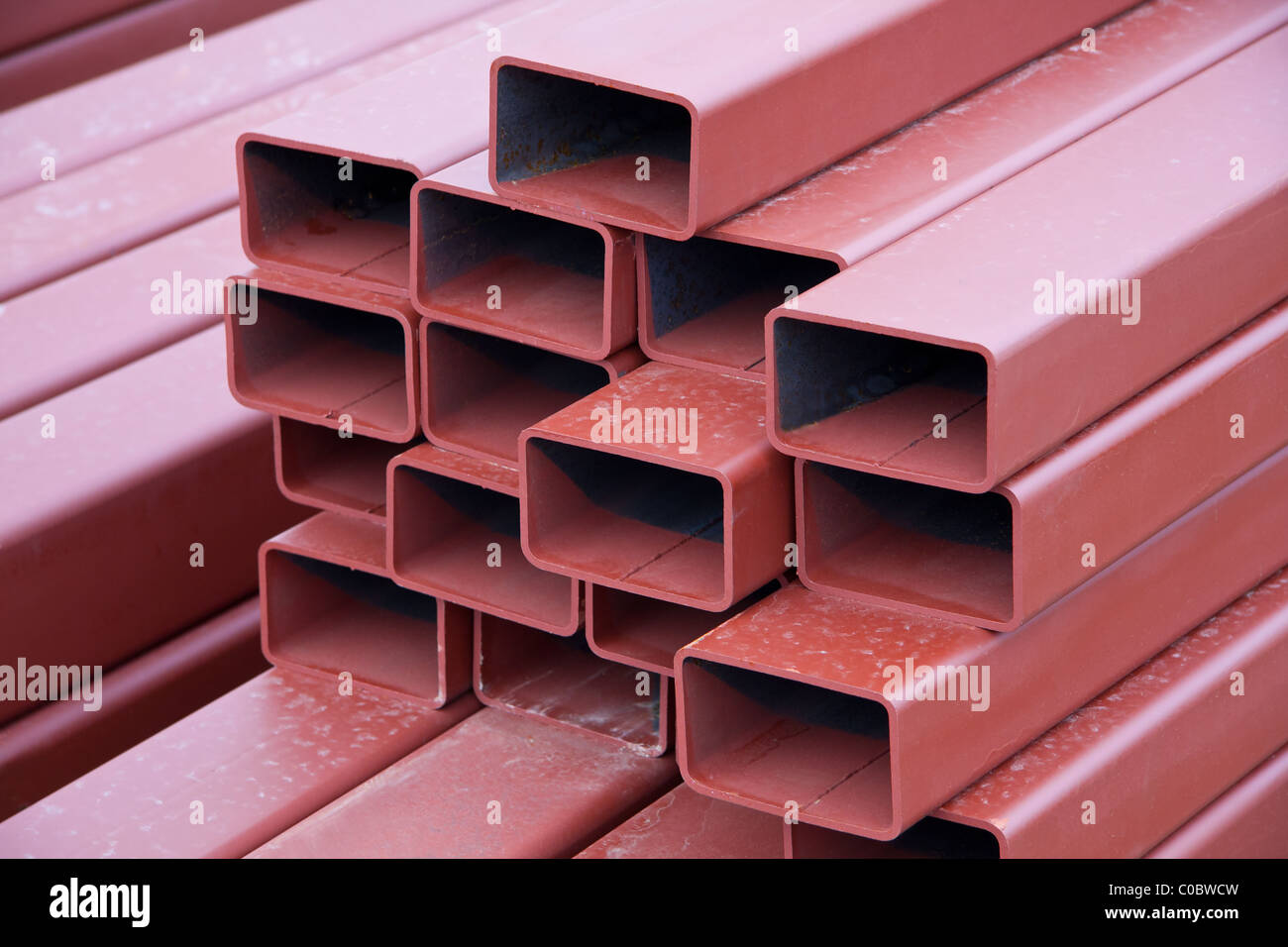 A stack of painted steel beams used in construction Stock Photo