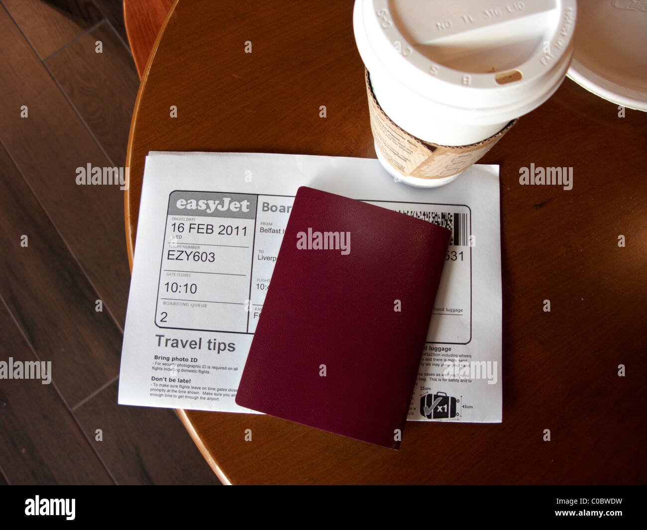 coffee passport and printed boarding card on a table at Belfast International Airport Northern Ireland - Stock Image