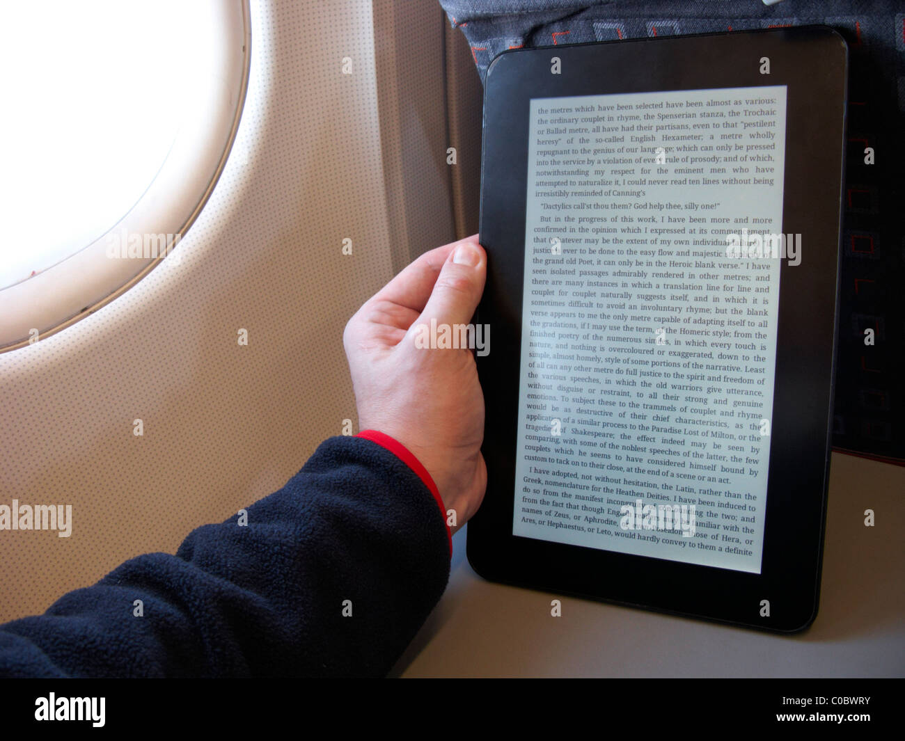 man reading an electronic ebook reader on board an aircraft - Stock Image