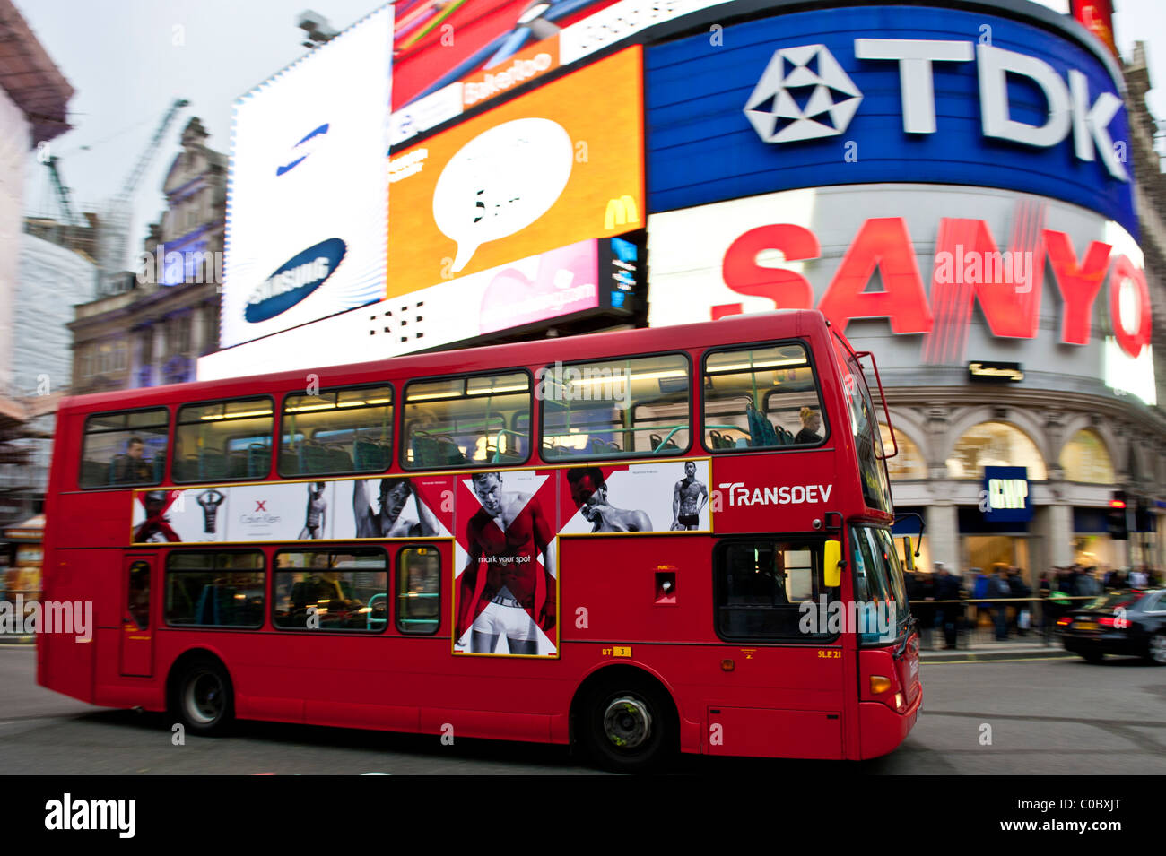 double decker red bus in front of the advertisings of Piccadilly circus, London, England, UK - Stock Image