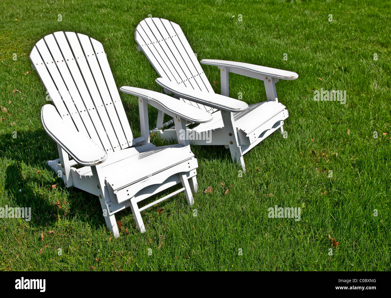 Two Adirondack Chairs On A Green Lawn
