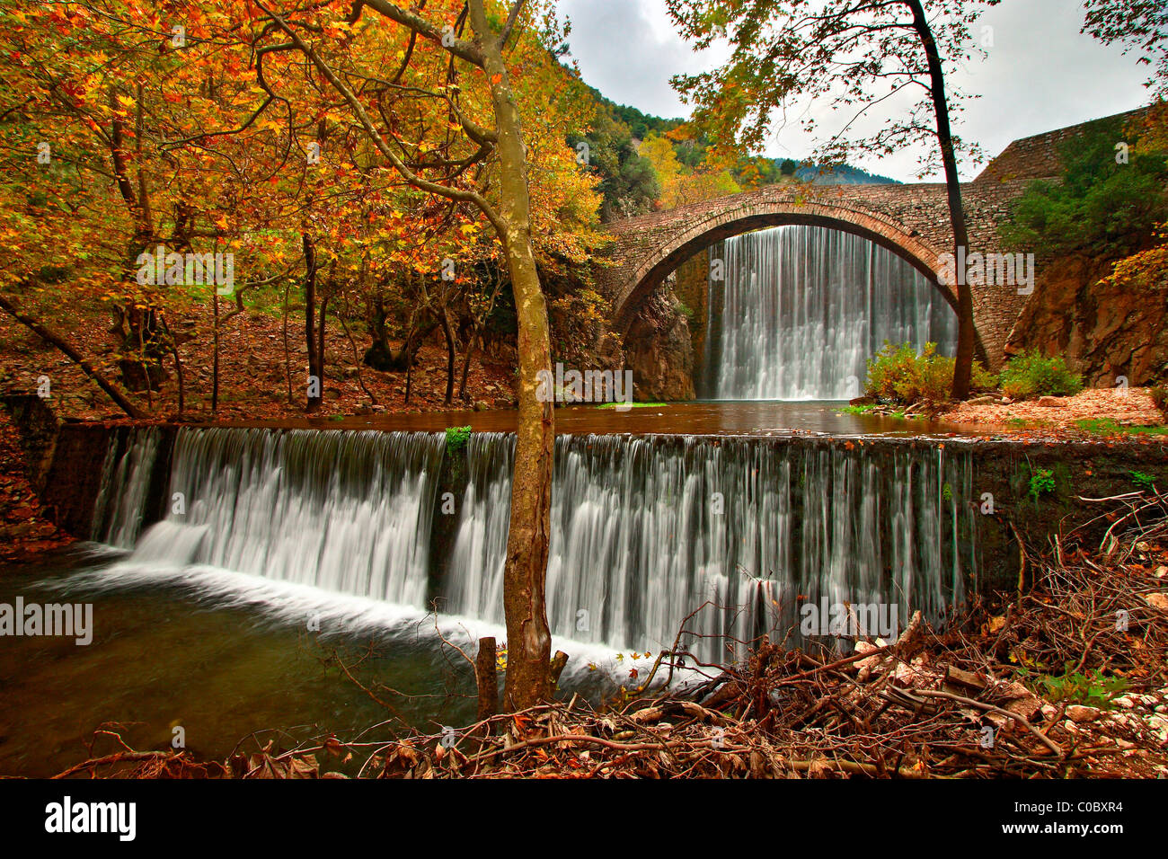 An old stone, arched bridge, between two waterfalls in Paleokarya, Trikala prefecture, Thessaly, Greece - Stock Image