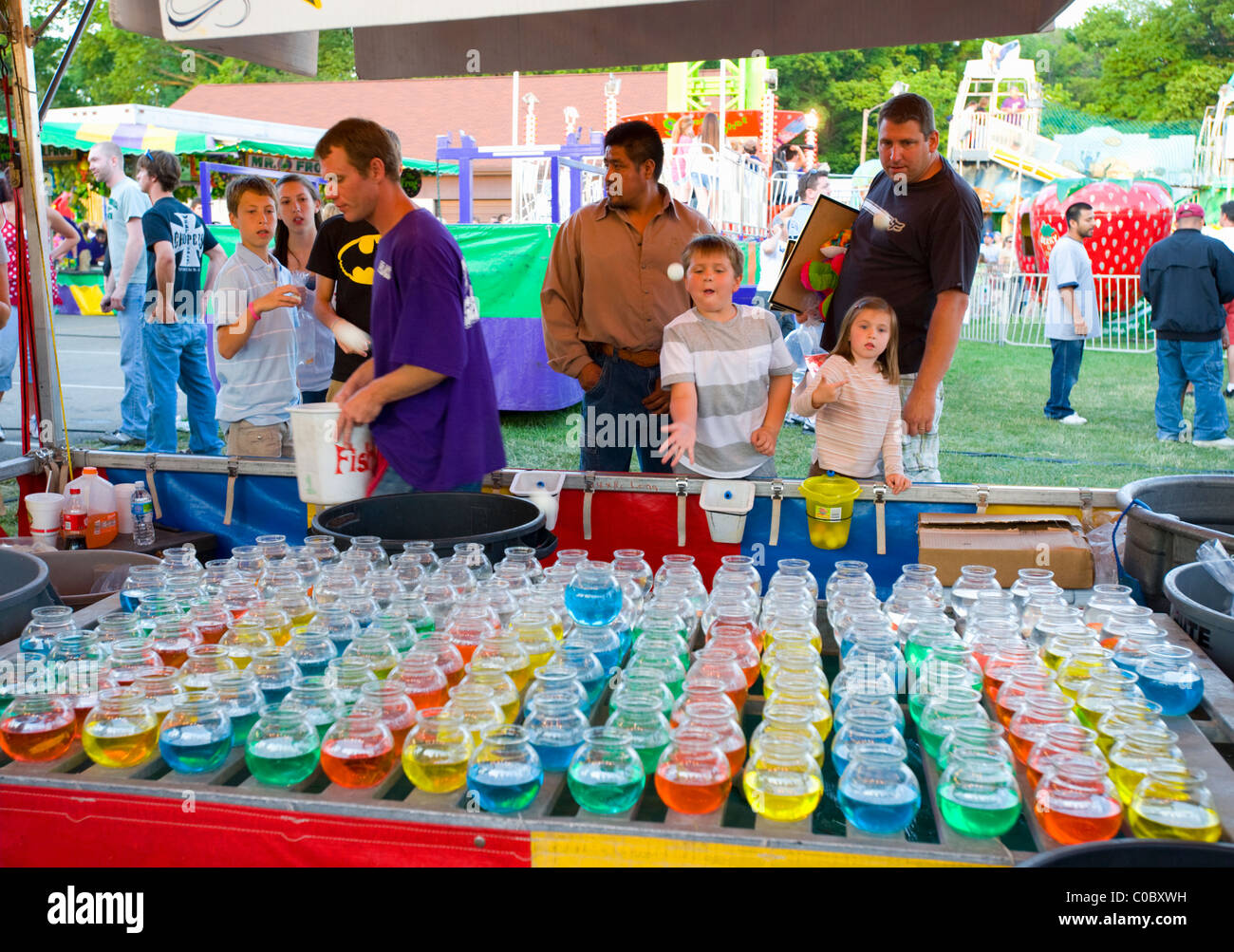 Children trying to win goldfish at local county fair in Indiana.  Ping pong balls are bounced into fishbowls to - Stock Image