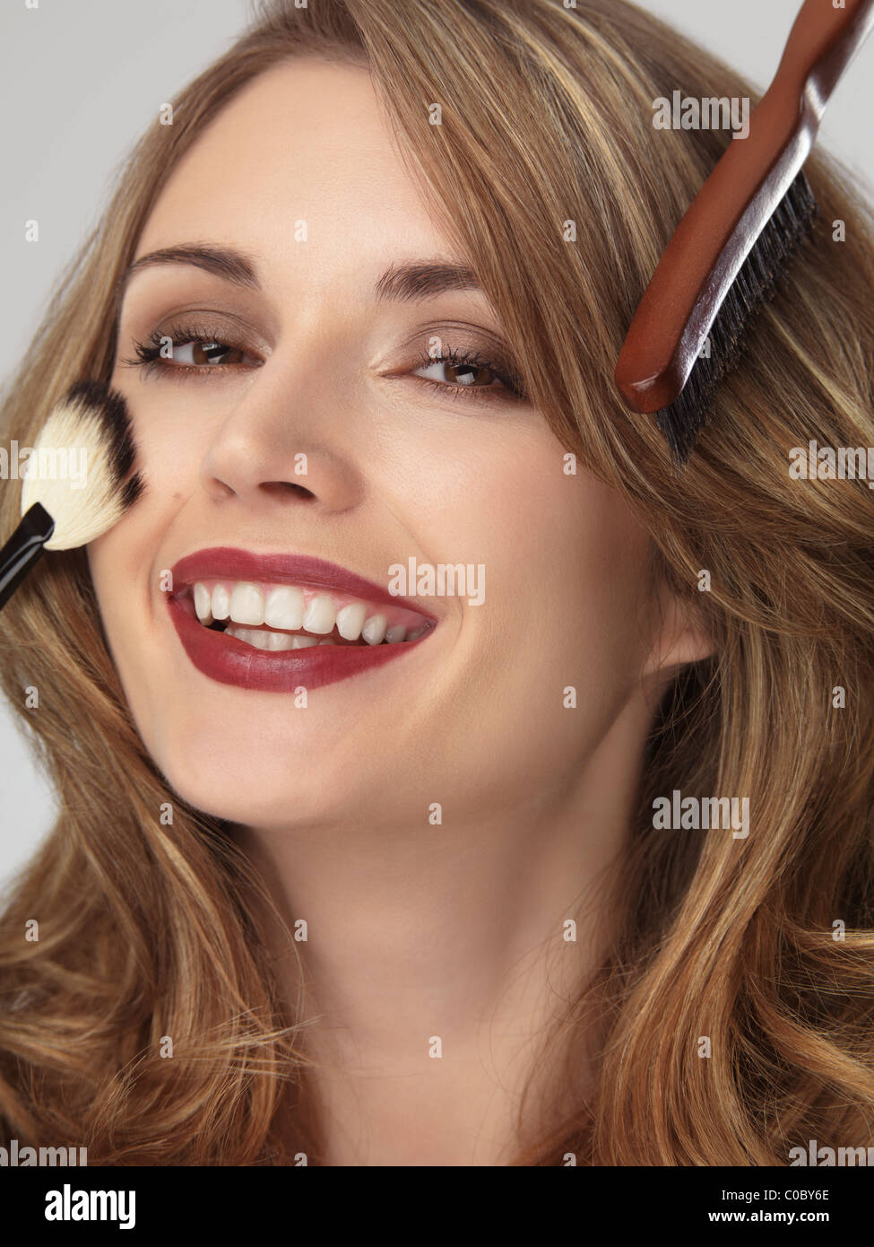 Portrait of a beautiful smiling young woman with her hair and makeup being done - Stock Image
