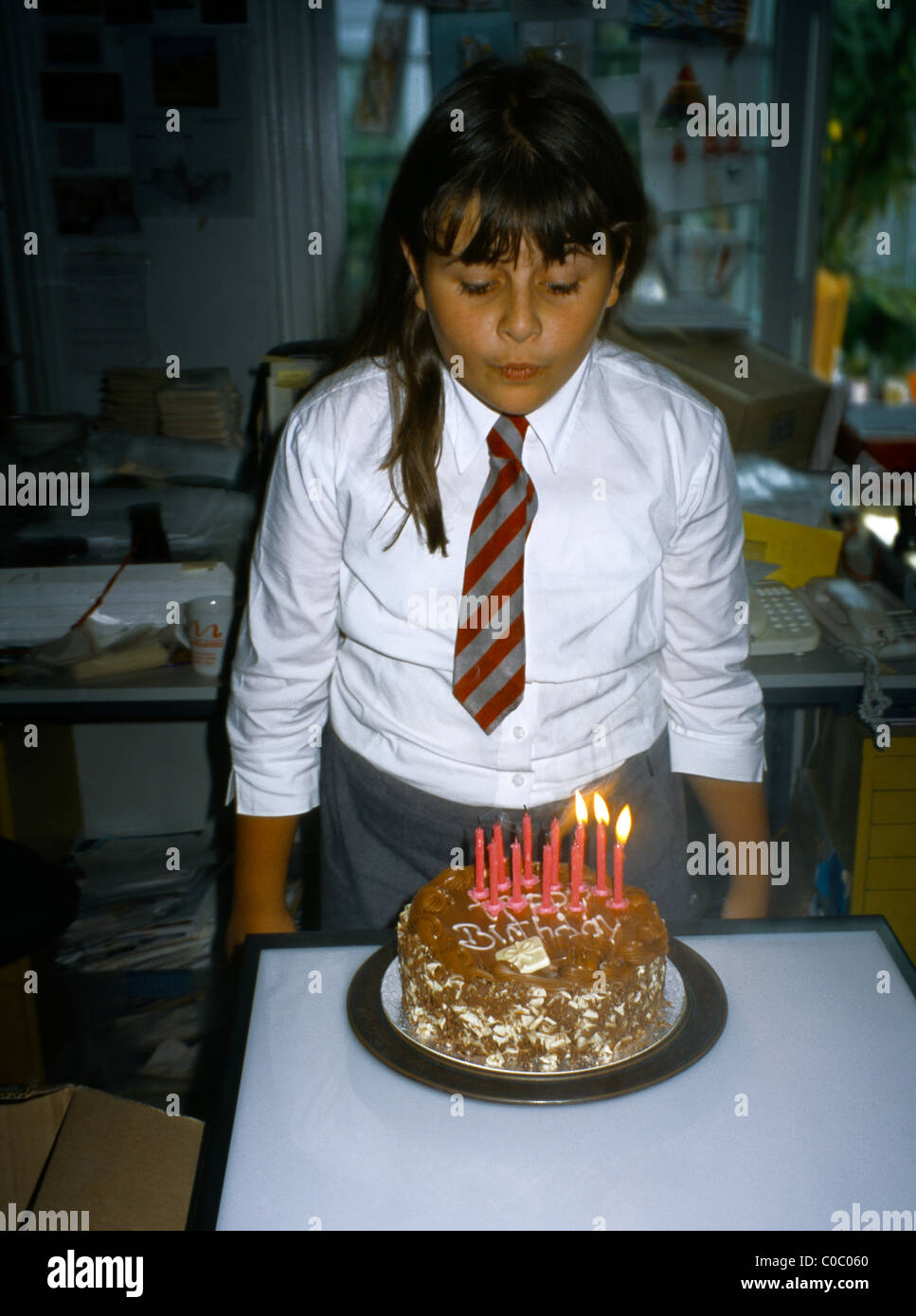11 Year Old Girl Blowing Out Candles On Her Birthday Cake