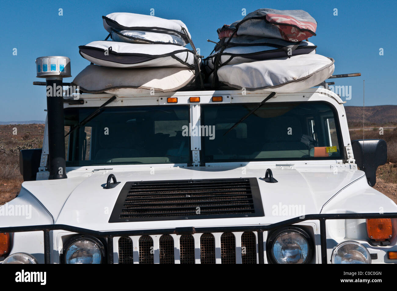 H1 Hummer with surfboards on the roof, Punto San Carlos, Baja California, Mexico - Stock Image