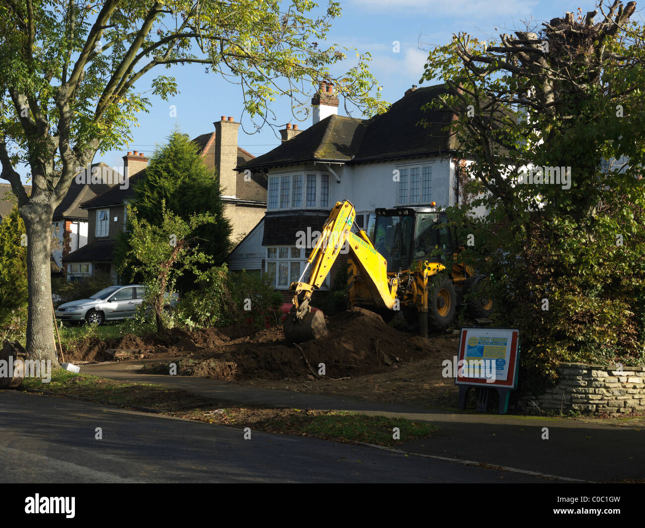 JCB Digger Working In Front Garden By House England - Stock Image