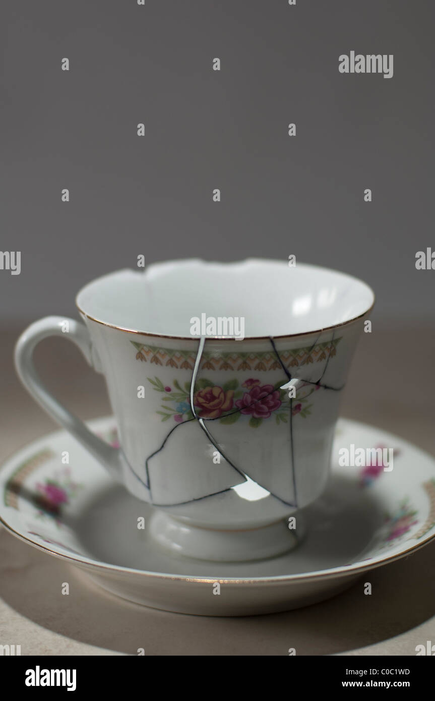Clumsily repaired leaky teacup with cracks - Stock Image
