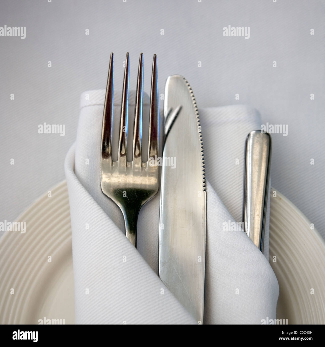 Table setting of Cutlery wrapped in cloth napkin on plate Stock ...