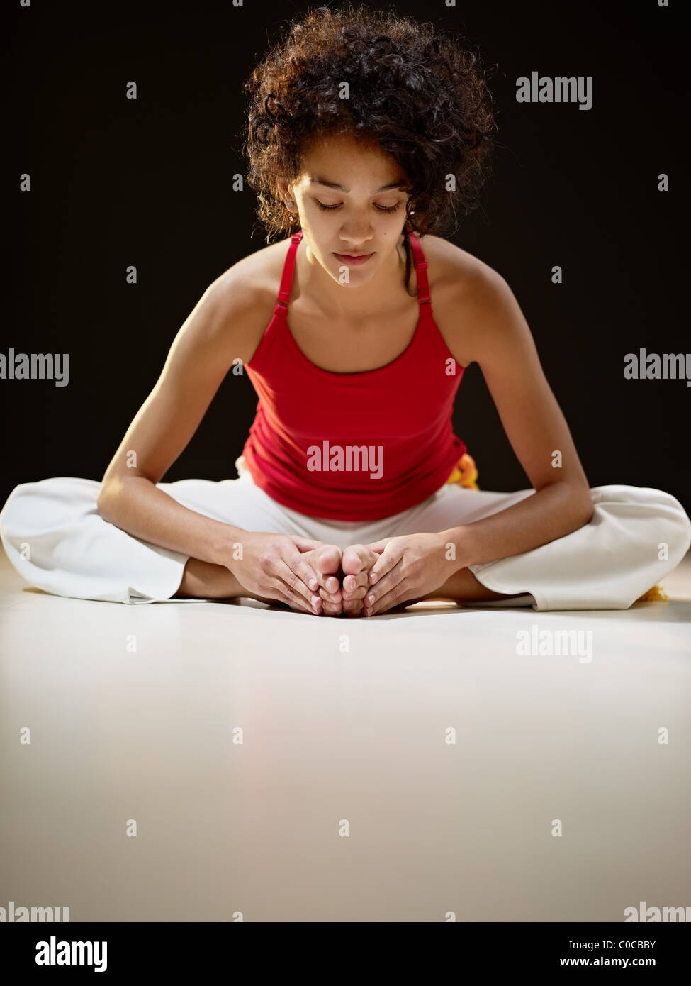 portrait of young adult latin american female sitting on white floor doing yoga exercise. - Stock Image