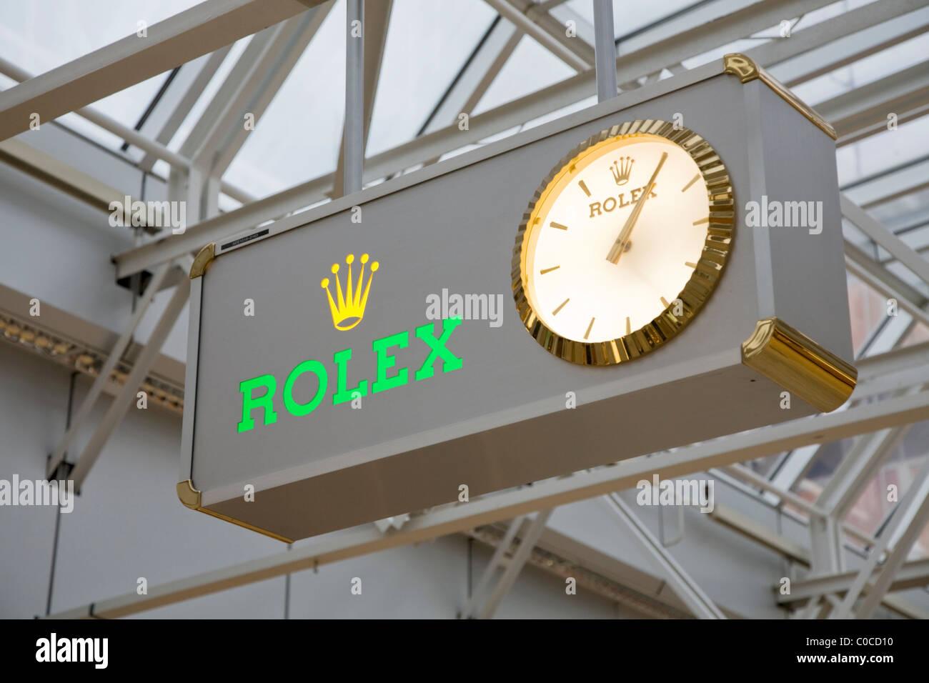 Display clock advertising Rolex brand of watches. International terminal departure hall, Geneva / Geneve Airport, Stock Photo