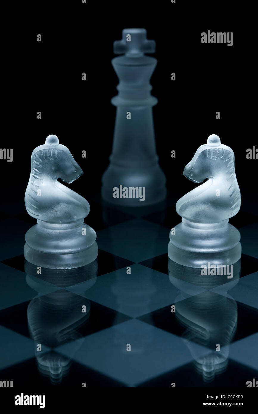 Macro shot of glass chess pieces against a black background - Stock Image