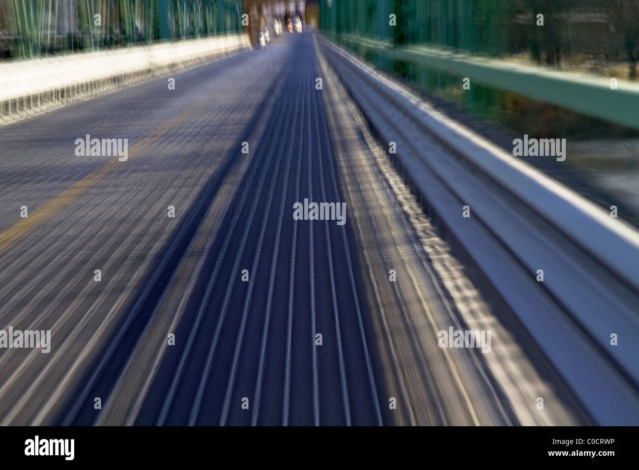 Motion blur of country bridge taken to create metaphor of path, journey, and approaching, differentiated lights - Stock Image