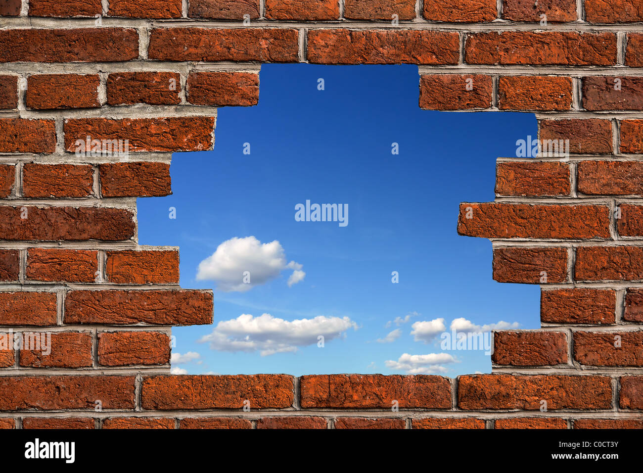 Blue sky seen through a hole made in the brickwall - Stock Image
