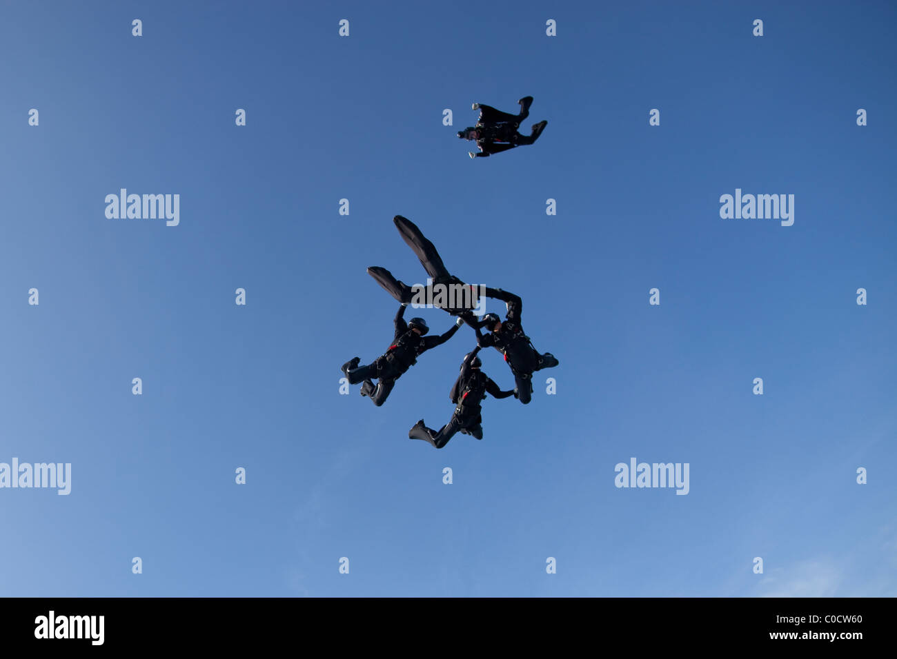 Professional formation skydivers are holding each other together and get filmed by a camera flyer. - Stock Image