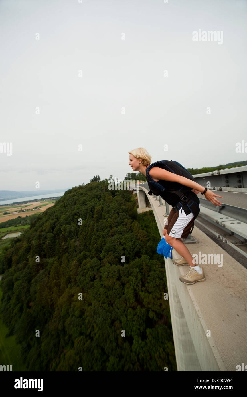 BASE jumper girl is going to diving from bridge with a parachute on her back. - Stock Image