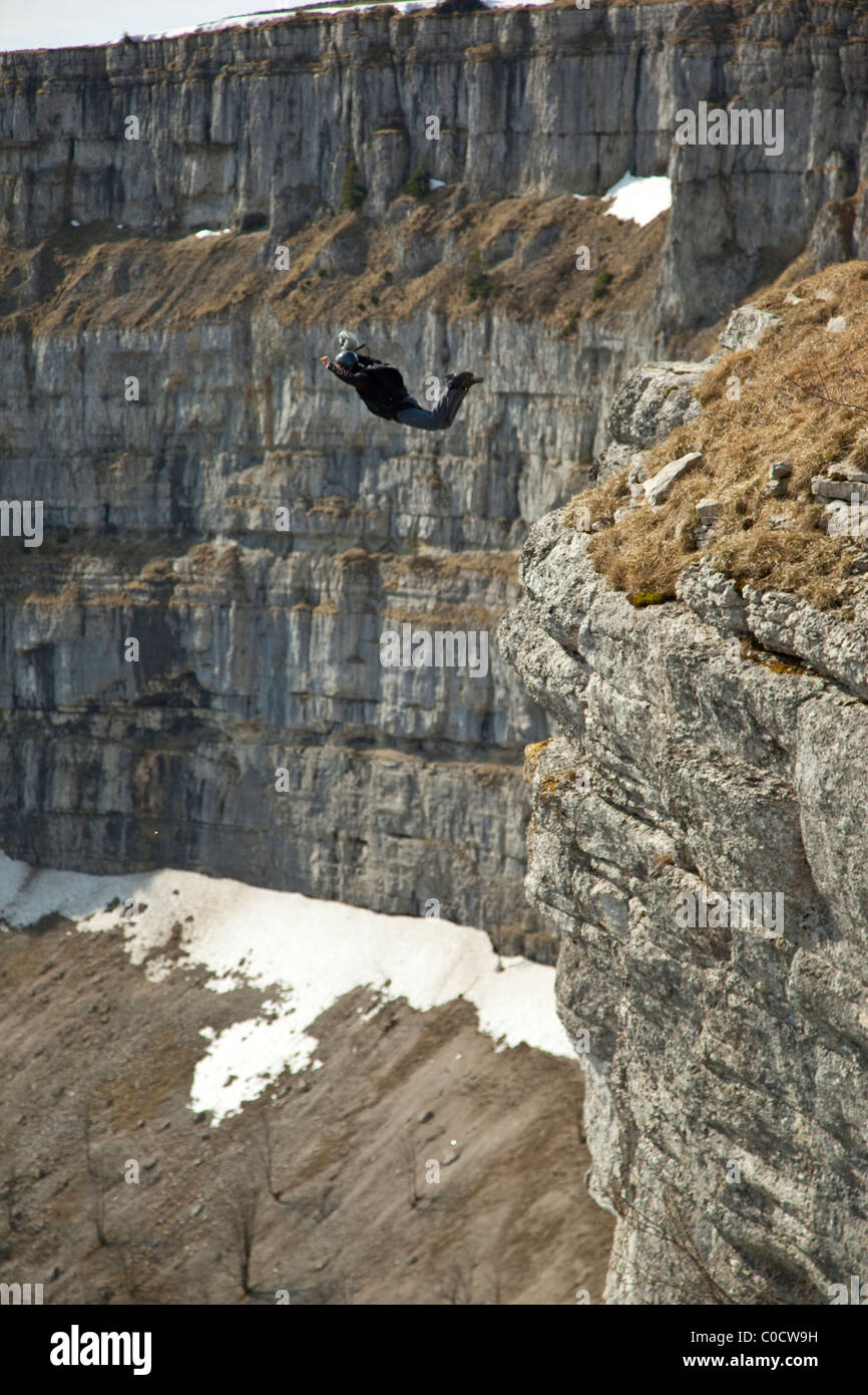 BASE jumper is diving from a cliff into the valley. - Stock Image