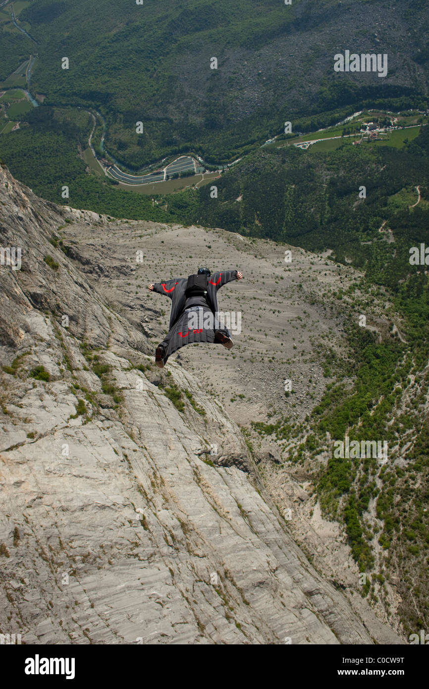 BASE jumper within a wingsuit is diving from a cliff and flys down the valley. - Stock Image