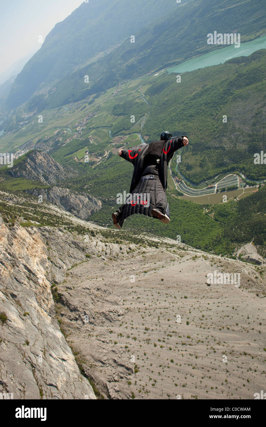 BASE jumper within a wingsuit is diving from a cliff and flys down the valley. Stock Photo