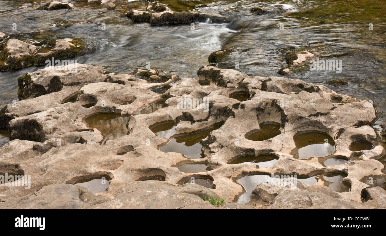 River bed erosion pattern made by small pebbles swirling around on the limestone. River Ure, Aysgarth, UK Stock Photo