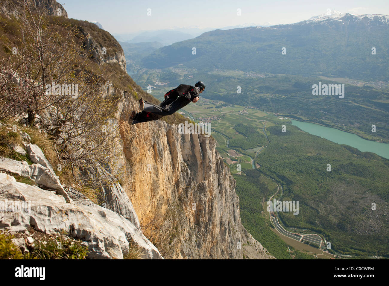 BASE diver within a wingsuit jumps from cliff and flys down the valley. - Stock Image