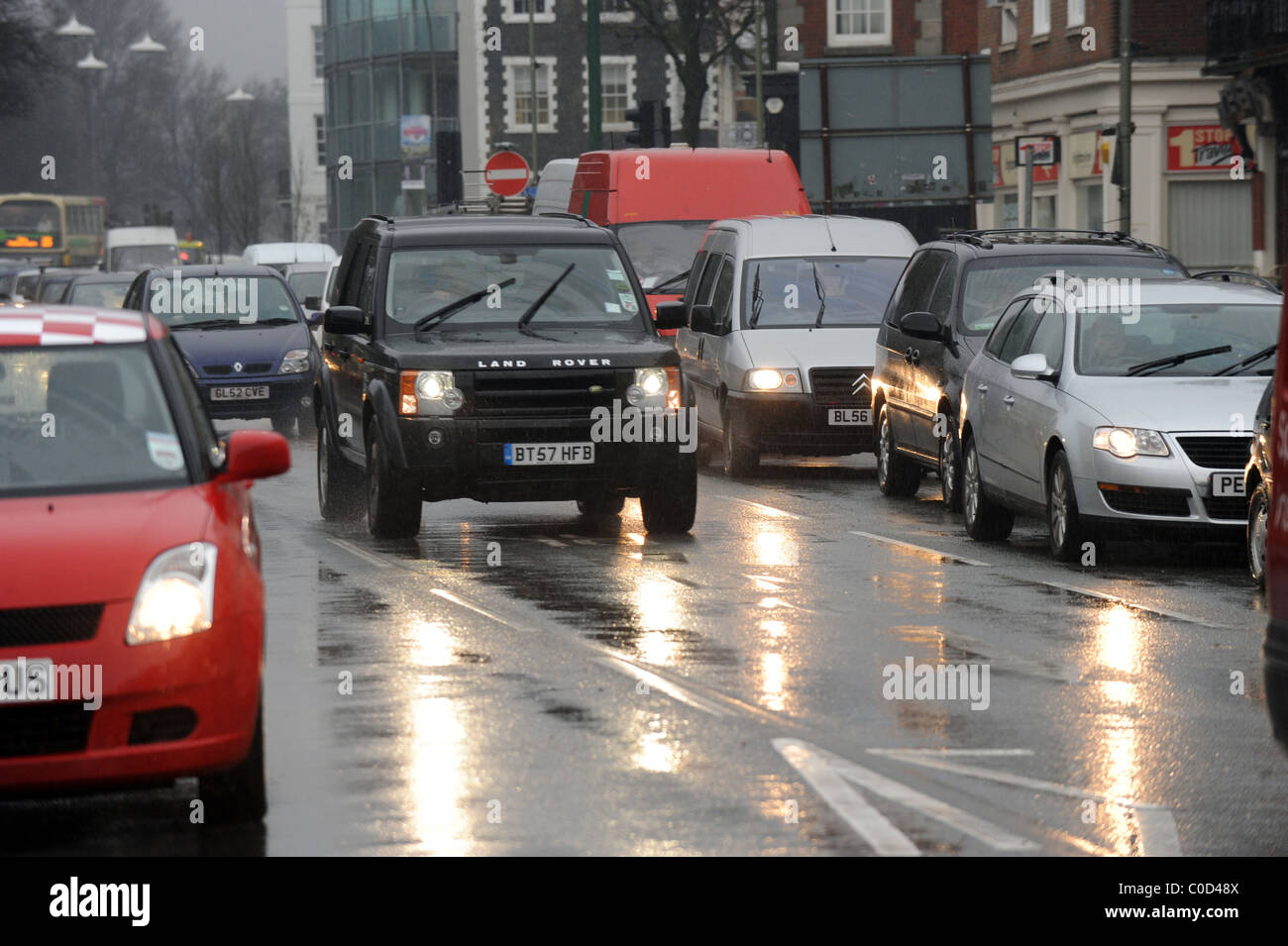 Traffic drives though the rain in the centre of Brighton at rush hour Stock Photo