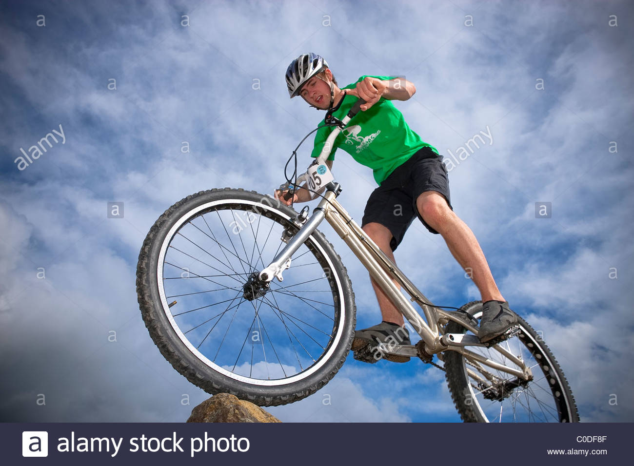 Trials rider performing tricks on bike - Stock Image