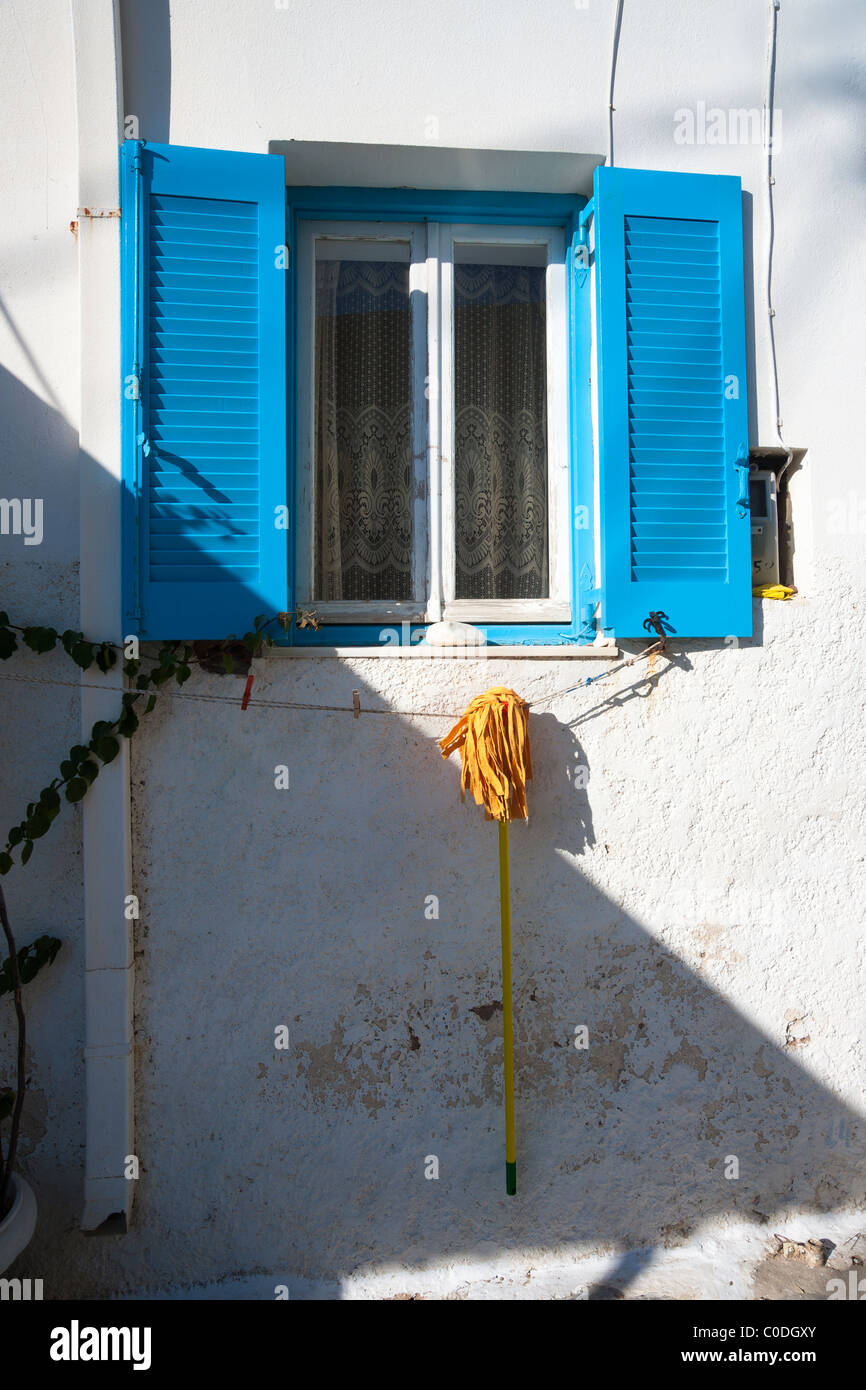 Yellow mop hung to dry below a blue shuttered window, on an exterior wall of a house in Naoussa, Greece. - Stock Image
