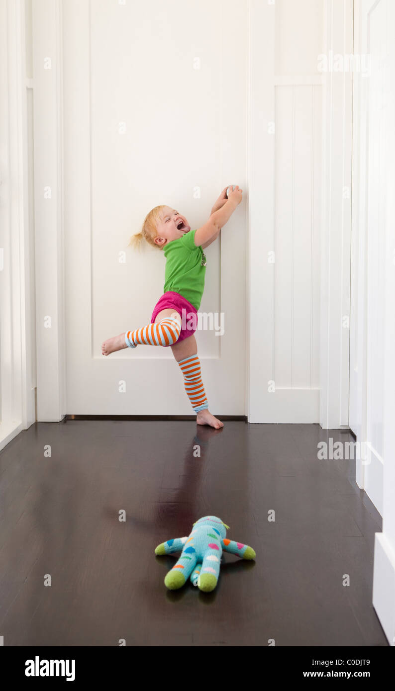 Little girl trying to get in closed door - Stock Image