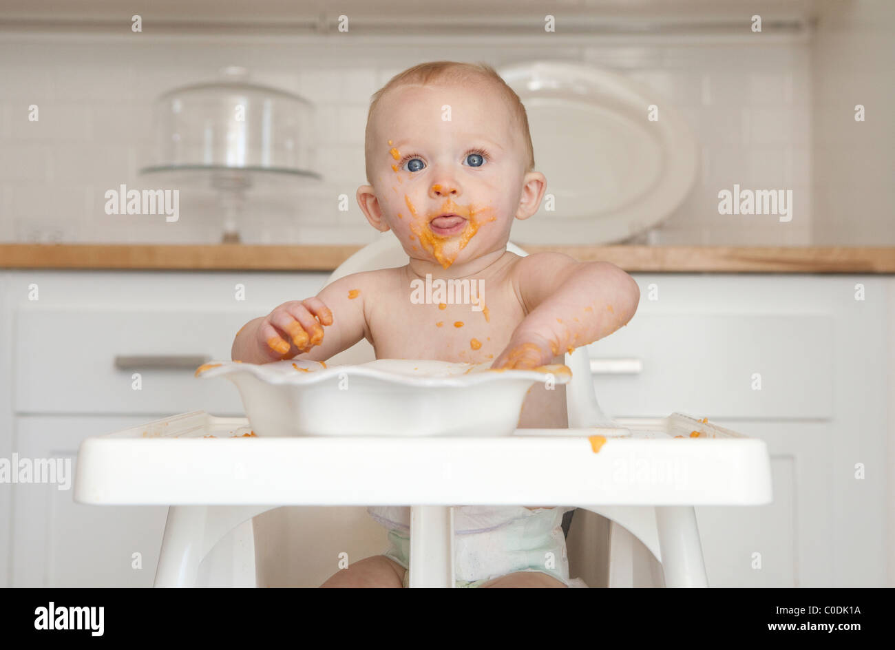 Messy baby eating in high chair - Stock Image