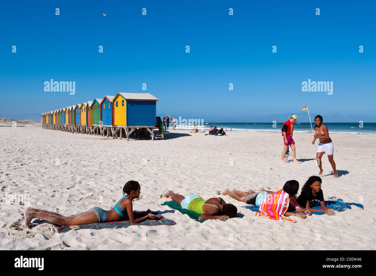 Girls sunbathing in front of beach huts in Muizenberg Cape Peninsula South Africa - Stock Image