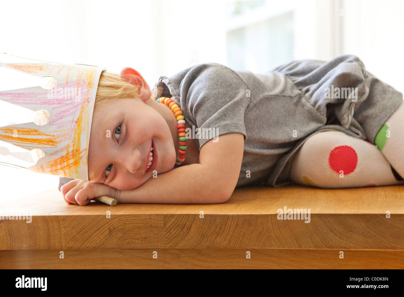 Little girl with homemade crown and candy necklace - Stock Image
