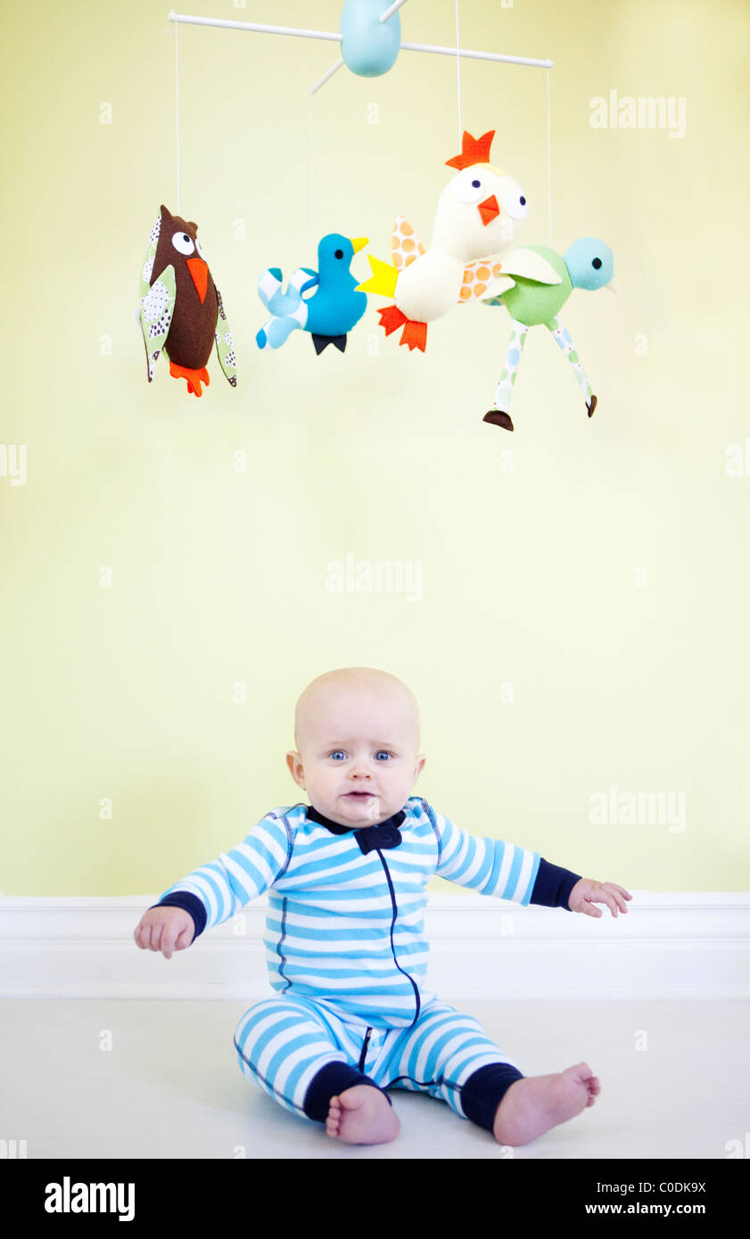 Baby boy sitting beneath mobile - Stock Image