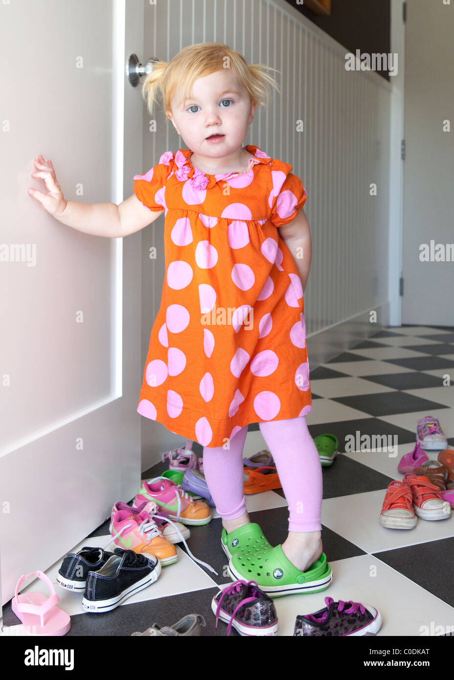 Little girl deciding which shoes to wear - Stock Image